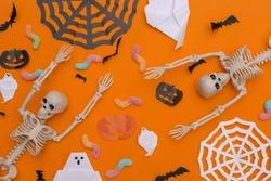Handmade Halloween decor and skeleton, gummy worms on orange background. Halloween background. Top view. Flat lay