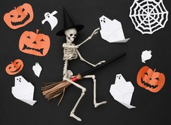 Handmade Halloween paper cut decor and skeleton on broomstick. Black background. Halloween background. Top view. Flat lay