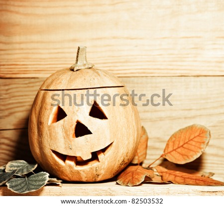Handmade Halloween pumpkin on wooden background. Autumn holidays concept