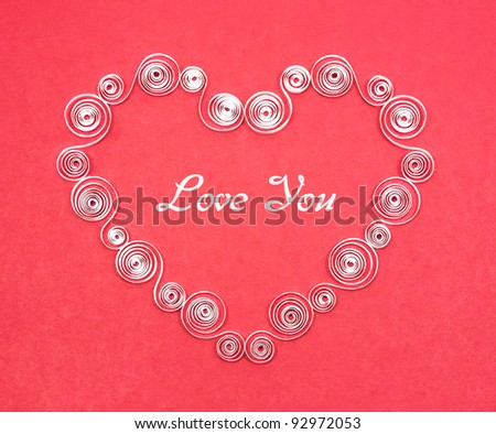 Handmade heart cut from white paper on red background. Quilling.