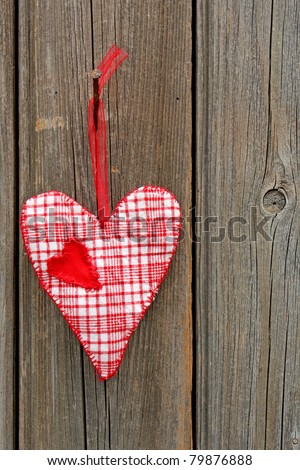Handmade heart of scrim hanging on old weathered wooden wall