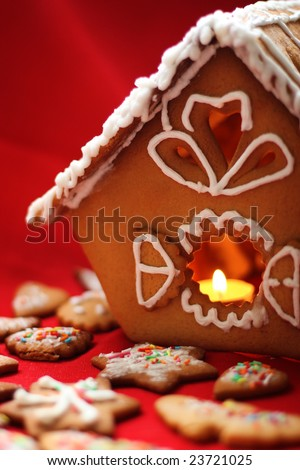handmade honey cake house with a candle close up over red