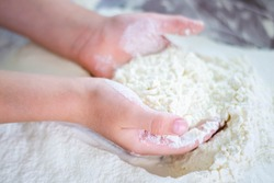 Handmade in the kitchen. Children's hands knead flour. Little helper in the kitchen. Home baking. Preparation of bread, pies and cakes. White flour on a brown silicone mat.
