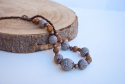 Handmade jewelry of polymer clay. Indian beaded necklace near bronze bowl. Luxury bohemian jewelry.