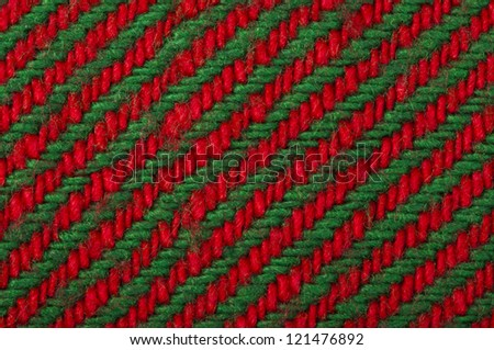 Handmade knit green and red background. Close up structure of the yarn. Christmas colors