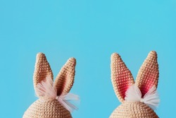 Handmade knitted amigurumi toy. Bunny ears with bows on the blue background. Crochet stuffed animals.