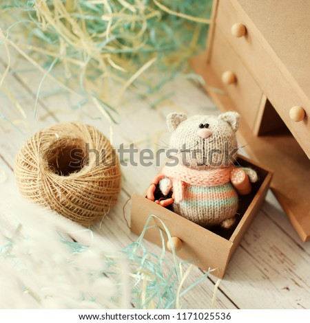Handmade knitted toy.  A knitted cat in a striped sweater holds sausage and  hot dog. The cat glutton