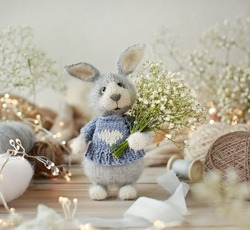 Handmade knitted toy. Grey rabbit on a background of balls of yarn.