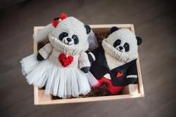 Handmade knitted toy. Pandas. Amigurumi  toys in black jacket, red trousers, white sweater and in the white dress on the wooden  background. Crochet stuffed animals. Married couple