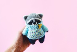 Handmade knitted toys. Amigurumi. Raccoon toy in the blue knitted sweater on the pink background. Crochet stuffed animals.