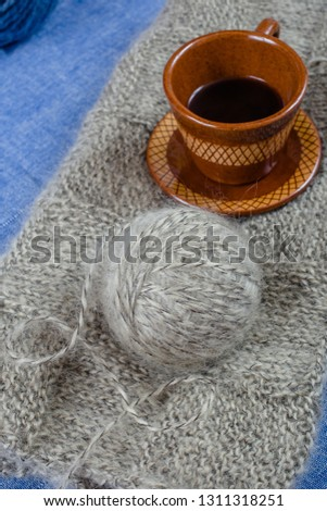 Handmade knitting fabric grey mohair, a ball of yarn and a cup of coffee on a blue background