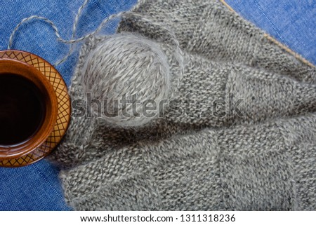 Handmade knitting fabric grey mohair, a ball of yarn and a cup of coffee on a blue background, top view close-up