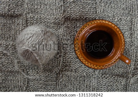 Handmade knitting fabric grey mohair, a ball of yarn and a cup of coffee, top view close-up