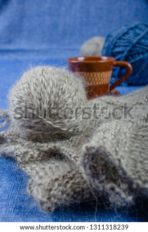 Handmade knitting fabric grey mohair, a cup of coffee and balls of yarn on a blue background, front view