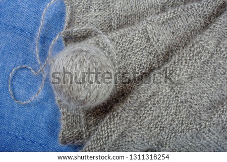 Handmade knitting fabric grey mohair and a ball of yarn on a blue background, top view close-up