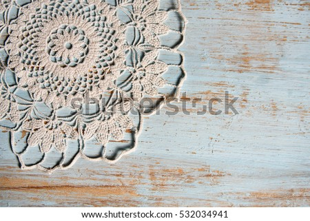 handmade lace on shabby chic, painted, blue wood. Macrame close-up, top view with copy space. Wedding or holiday background.  #532034941