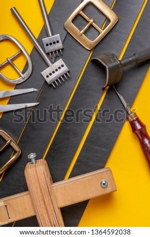 Handmade leather craft tools, belt buckle and black leather straps on yellow background #1364592038