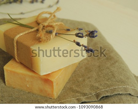 Handmade natural bath spa soap on linen towel, wooden background. Soap making. Soap bars. Spa, skin care. Gift wrapping.