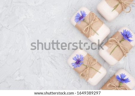 Handmade natural soap set border decorated with craft paper, scourge and blue cornflowers on gray stone backgroun . Organic cosmetics, zero waste, eco friendly concept. Top view Flat lay Copy space.