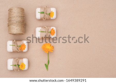 Handmade natural toilet soap set decorated with craft paper, tied with scourge, calendula flowers and skein of twine. Organic cosmetics, zero waste, eco friendly concept. Top view Flat lay Copy space.