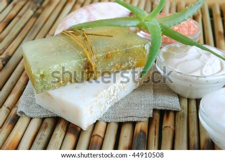 Handmade oatmeal soaps, facial mask, salt and hand cream on green on bamboo mat