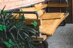 Handmade old recycled wooden and metal furniture, eco-friendly manufactory, mattress sits and pillows on the bench made of recycled coffee sacs and bags, alternative solution and decor for garden