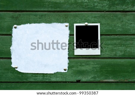 Handmade paper and instant photo on green wooden background