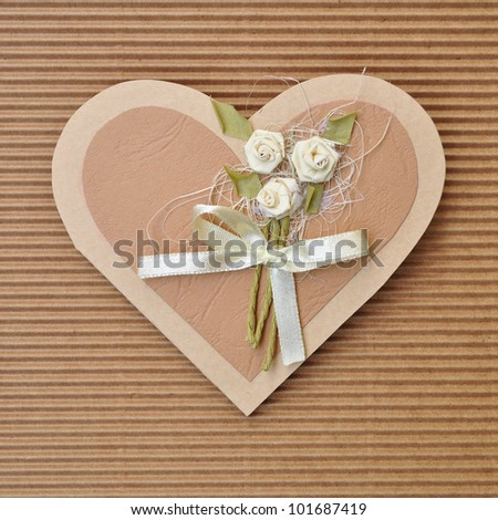 Handmade paper card love heart shape decorated with flowers and a bow brown colors.