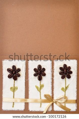 Handmade paper card with coffee beans flower design and a bow. Album book cover abstract background.