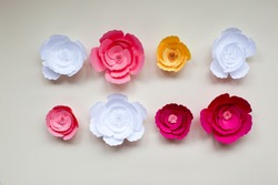 Handmade paper flowers on paper background, white and pink roses, decor for invitation
