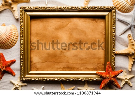 Handmade paper sheet in picture frame, shells and starfish on sand