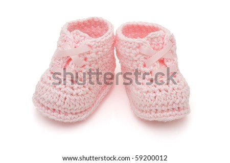 Handmade pink baby booties isolated on a white background