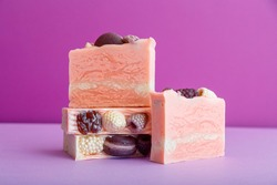 Handmade pink soap bars composition. Many craft artisan diy pink soap bars with berries on top on purple background. Natural skin care beauty bath products, homemade toiletries.
