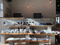 handmade porcelain arts by an artisan.cups, plates, bowls display on the wood stand with concrete bricks.