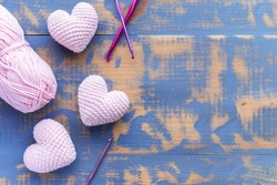 Handmade purple knitted three pink hearts with ball of yarn. Top view