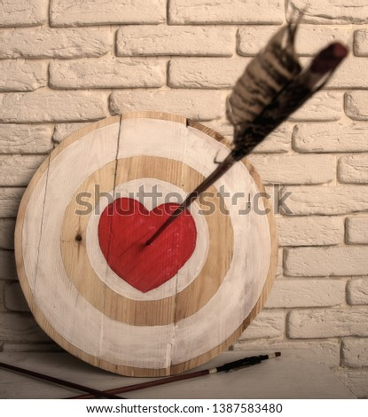 Handmade rough wooden target with a center in the form of a red heart and an arrow from a bow that hit the center and two arrows missed #1387583480