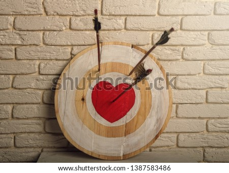 Handmade rough wooden target with a center in the form of a red heart and an arrow from a bow that hit the center and two arrows missed #1387583486