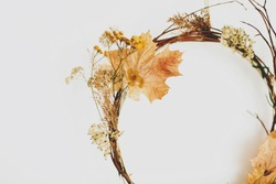 Handmade rustic autumn wreath on white wall. Rural seasonal wreath made of autumn leaves, twigs and flowers. Hello Autumn and Happy Thanksgiving decor, celebrating at home