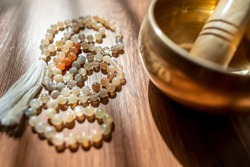 Handmade sacred mala seed beads and a golden Tibetan bowl on a wooden background in the soft and beautiful light of morning, a perfect time for a yoga session acompanied by healing sounds.