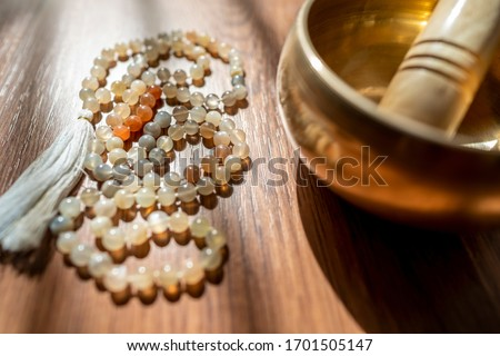 Handmade sacred mala seed beads and a golden Tibetan bowl on a wooden background in the soft and beautiful light of morning, a perfect time for a yoga session acompanied by healing sounds. Stock photo ©
