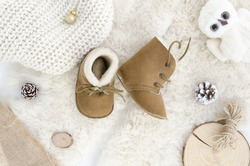 Handmade Sheepskin Baby Boots, Slippers, shoes, Moccasins.Brown genuine leather soft natural. Winter concept flat lay kids Newborn. Top view. Baby Shower