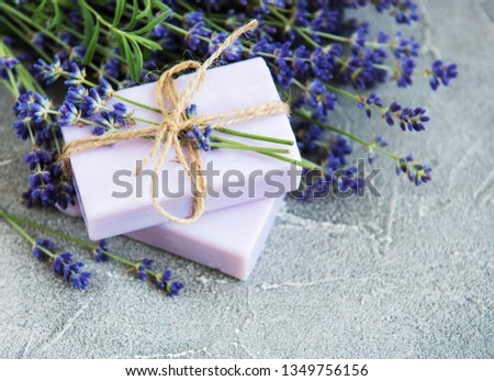 Handmade soap and lavender flowers on a concrete background