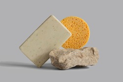 Handmade soap bar, yellow sponge laying, balancing on rock, gray background, copy space. Solid shampoo, oil on podium. Organic, natural cosmetic. Beauty, skincare product