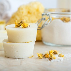 Handmade soap round bars with herbs dry marigold flowers. Spa bathroom products aroma salt, natural washcloth on marble table. Home made diy beauty cosmetics spa wellness products. Square closeup