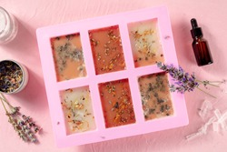 Handmade soap, the process of making. Glycerin with herbs, poured into a special mold for drying, shot from the top on a pink background