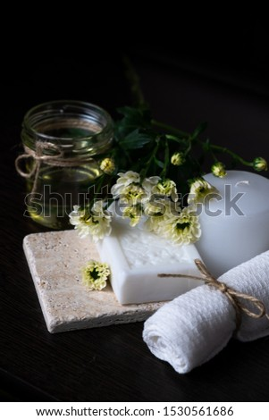 Handmade soap with a pattern lies on the table.  On a black table lies handmade soap, flowers and olive oil.  Collection of items for the bathroom