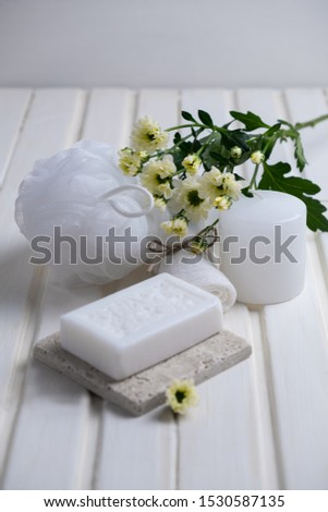 Handmade soap with a pattern lies on the table.  On a white table is handmade soap, a towel, flowers and a washcloth.  Collection of items for the bathroom