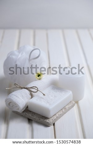 Handmade soap with a pattern lies on the table.  On a white table is handmade soap, a towel and a washcloth.  Collection of items for the bathroom