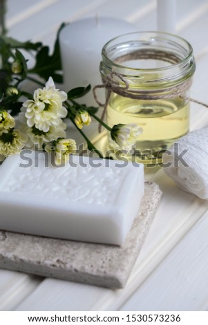 Handmade soap with a pattern lies on the table.  On a white table is handmade soap, flowers and olive oil.  Collection of items for the bathroom