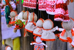 Handmade souvenir shop. Showcase with many fabric dolls in national costumes and wreaths of bright flowers. Dolls at the fair on the counter in the store.